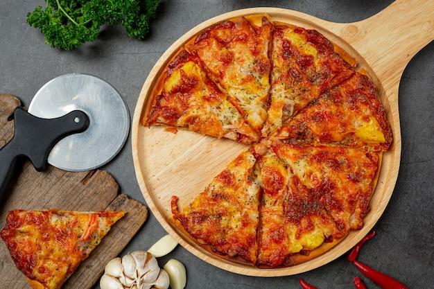 Deliziosa pizza hawaiana e ingredienti per cucinare.