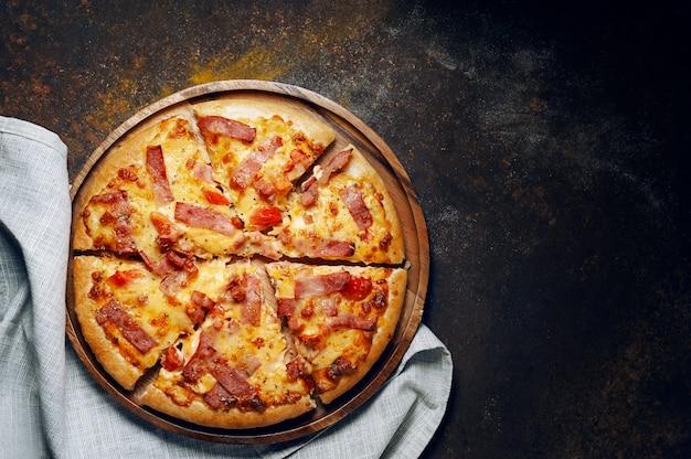 Deliziosa pizza italiana a fette di prosciutto, pancetta e formaggio con ingredienti alimentari sulla vecchia cucina