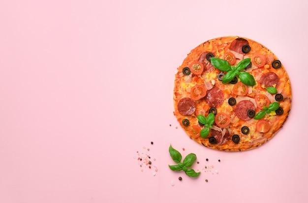 Deliziosa pizza italiana, foglie di basilico, sale, pepe su sfondo rosa