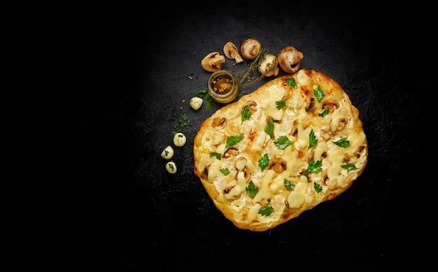 Deliziosa pizza quadrata appena sfornata con formaggio fuso e funghi su sfondo nero con ingredienti, vista dall'alto