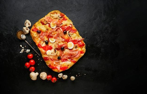 Deliziosa pizza quadrata appena sfornata con prosciutto, formaggio e olive con ingredienti, vista dall'alto