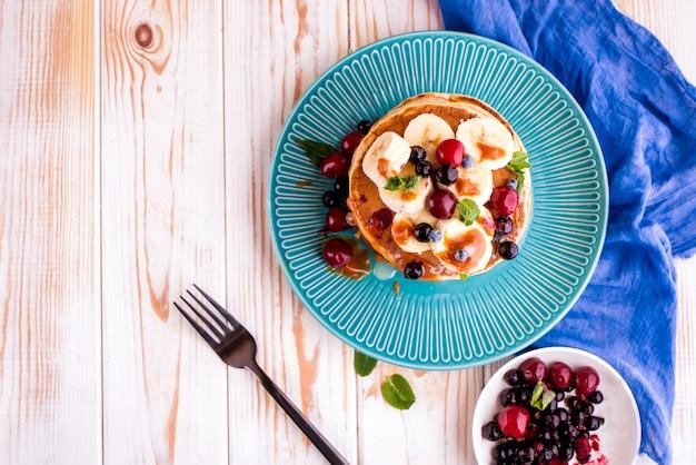 Deliziosa, sana, ricca colazione sul tavolo bianco.pancake con frutta, succo d'arancia. superiore