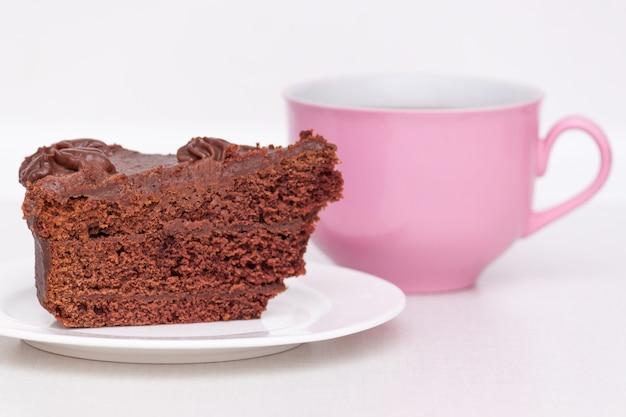 Deliziosa torta al cioccolato sul piatto con una tazza di caffè rosa sul tavolo su sfondo chiaro