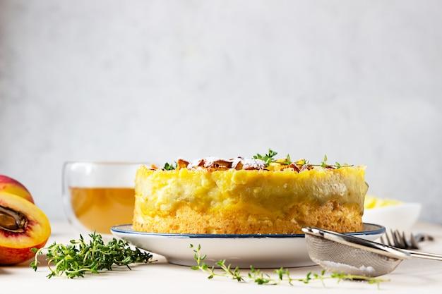 Deliziosa torta chiffon con crema pasticcera e pesche noci con tisana e timo.