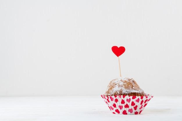 Deliziosa torta con cuore rosso sulla bacchetta