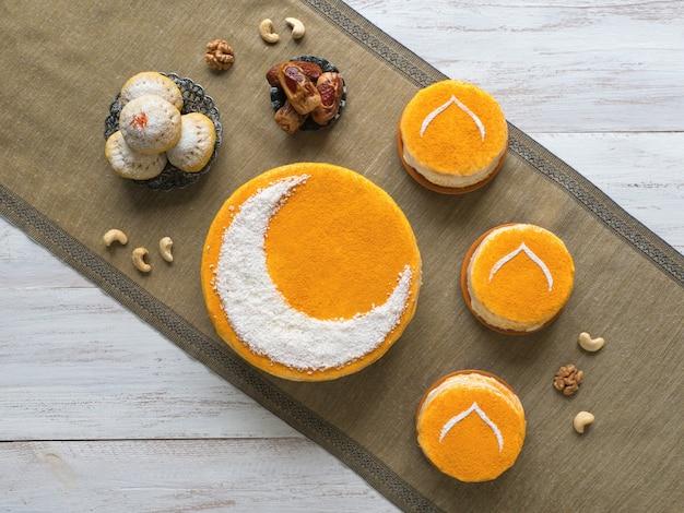 Deliziosa torta dorata fatta in casa con una luna crescente, servita con caffè nero e datteri. ramadan wall, copia spazio
