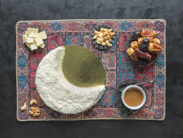 Deliziosa torta fatta in casa a forma di falce di luna, servita con datteri e tazza di caffè