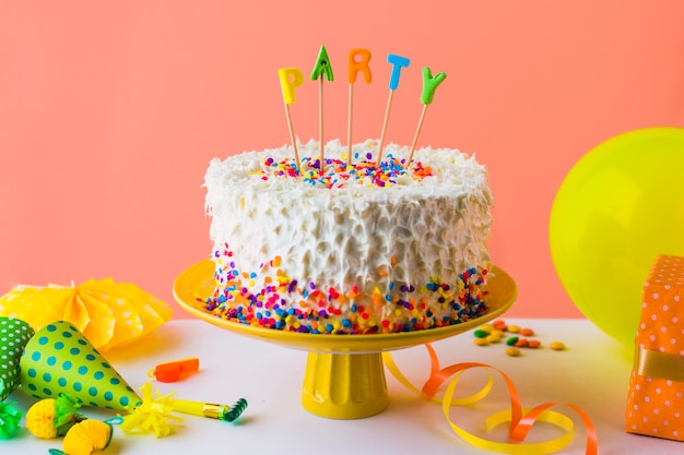 Deliziosa torta festa con accessori sul piano del tavolo bianco