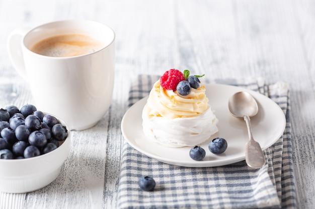 Deliziosa torta pavlova con panna montata e frutti di bosco freschi