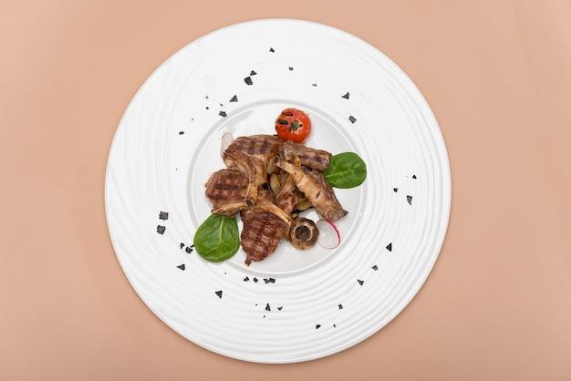 Deliziose costolette di agnello alla griglia, con pomodoro grigliato e decorato con ravanello, spinaci baby, foglia verde