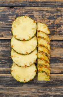 Deliziose fette di ananas piatte posate sul vecchio legno grunge