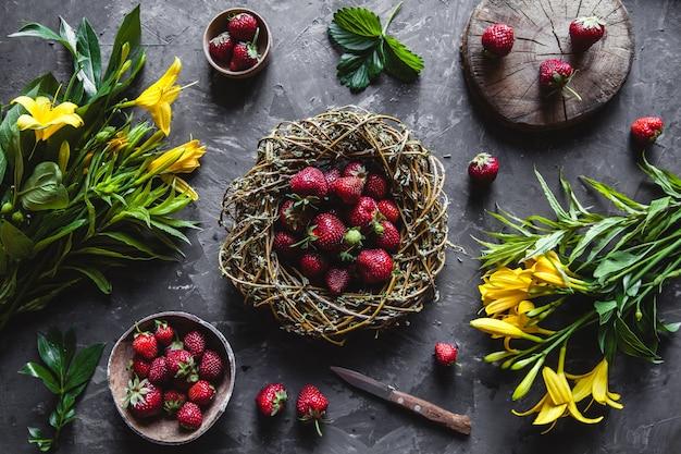 Deliziose fragole con fiori gialli su una superficie grigio scuro in una ghirlanda vintage. cibo sano, frutta