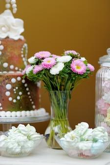 Deliziose meringhe alla fantasia in una ciotola di vetro e una grande torta (tavolo da sposa dolce)