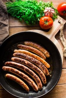 Deliziose salsicce fritte con crosta dorata in padella di ferro, pomodori freschi prezzemolo sul tavolo di legno