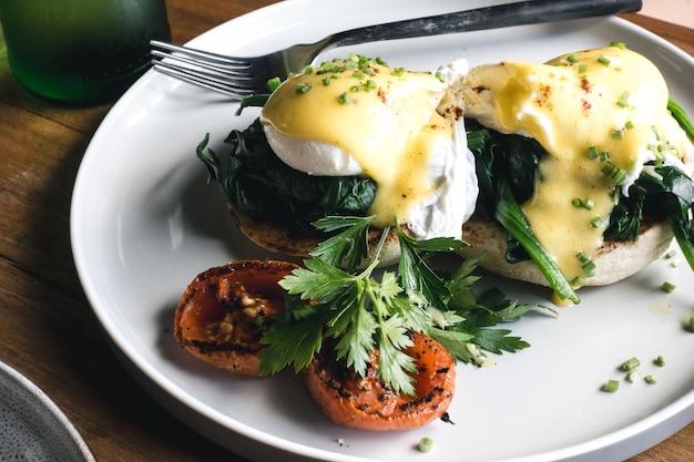 Deliziose uova in camicia su pane tostato con prezzemolo fresco e pomodori