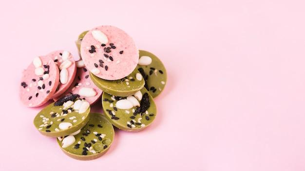 Deliziosi cerchi di cioccolato verdi e rosa decorate con semi su carta da parati rosa
