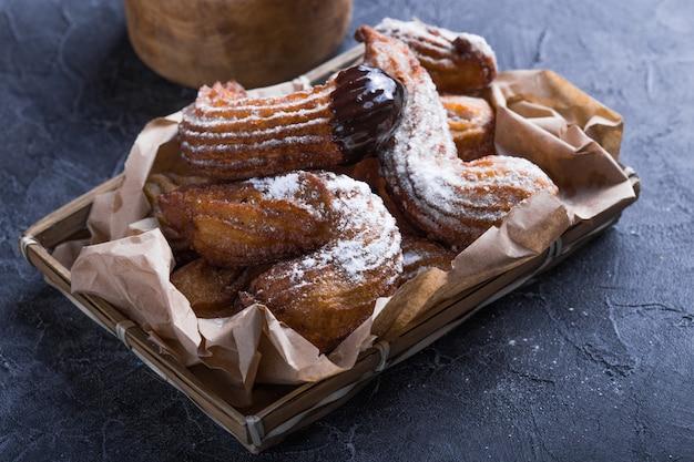 Deliziosi churros in padella fritti e spolverati con zucchero a velo