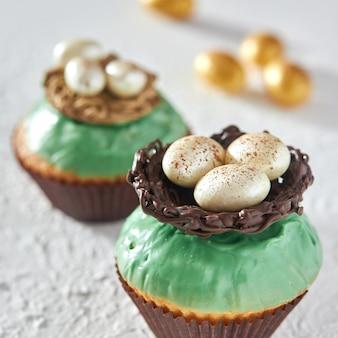 Deliziosi cupcakes decorati con glassa con un nido e uova di cioccolato