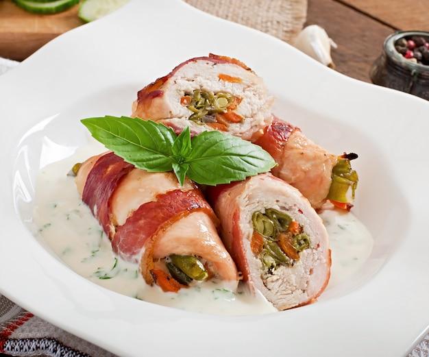 Deliziosi involtini di pollo ripieni di fagiolini e carote avvolti in strisce di pancetta