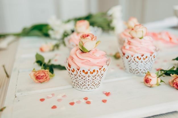 Deliziosi muffin gustosi con una crema rosa decorata con vero ros