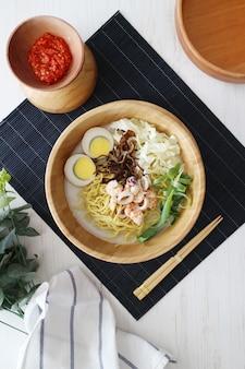 Deliziosi noodles con aglio aglio e verdure su una ciotola di legno con salsa di peperoncino