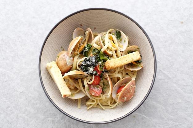 Deliziosi noodles di pasta fritta con vongole e pane