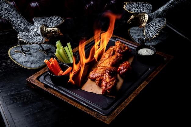 Deliziosi pezzi di ali di pollo grigliati con fiamme di fuoco. barbecue e grigliate. piatto del ristorante