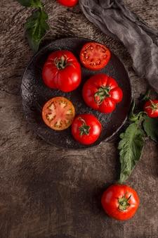 Deliziosi pomodori freschi sul piatto piatto laici