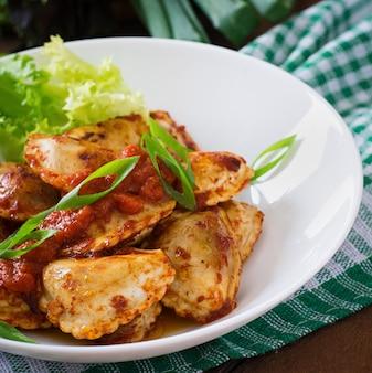 Deliziosi ravioli con salsa di pomodoro e cipolle verdi