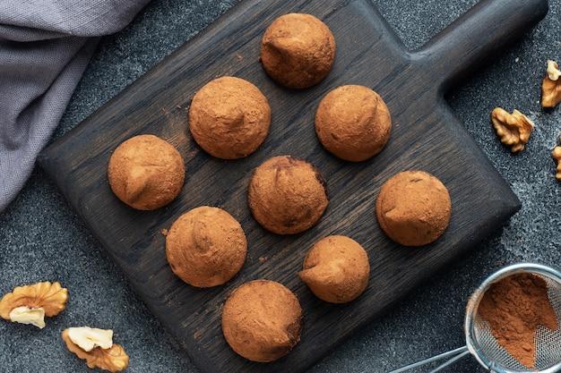 Deliziosi tartufi al cioccolato cosparsi di cacao in polvere e noci su un supporto di legno. sfondo scuro di cemento.