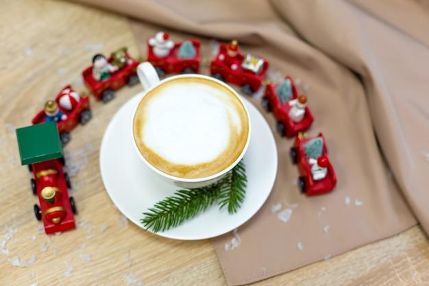 Delizioso caffè di cappuccino mattutino fresco festivo in una tazza bianca in ceramica sul tavolo di legno con trenino decorativo natalizio, ornamenti rossi, lucciole e rami di abete