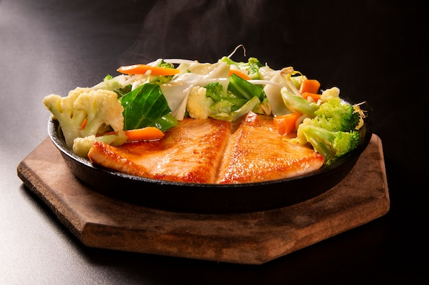 Delizioso cibo al salmone teppanyaki con le bacchette e la verdura nella padella di ferro.
