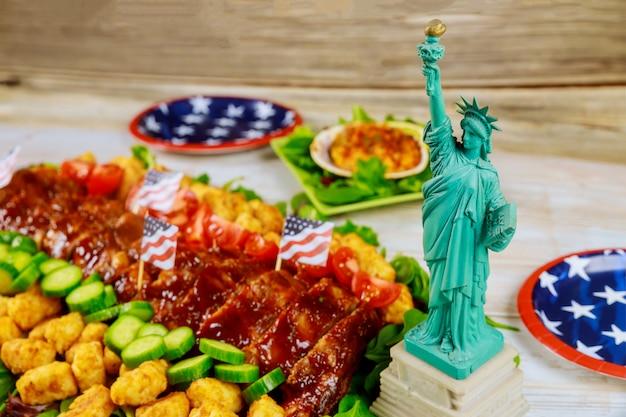 Delizioso cibo americano sul tavolo del partito con la statua della libertà.