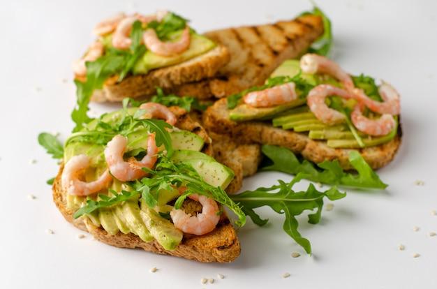 Delizioso cibo per il fitness. toast con avocado, gamberi e rucola su sfondo bianco.