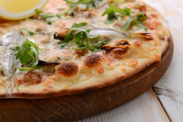 Delizioso cibo piccante italiano, pizza con acciughe e cetriolini, piatti piccanti caldi per buongustai
