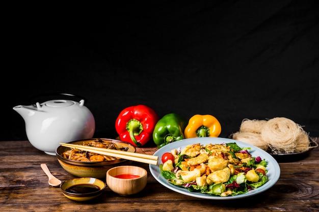 Delizioso cibo tailandese con salsa di soia; teiera e peperoni su scrivania su sfondo nero