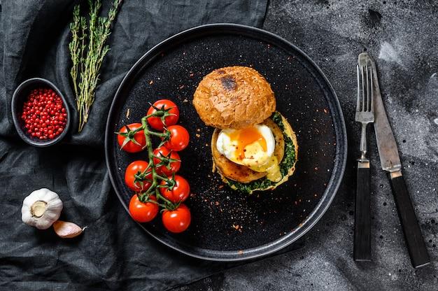 Delizioso fishburger con filetto di pesce, uova e spinaci su brioche.