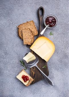 Delizioso formaggio gouda olandese con fette di formaggio, pane multicereali e marmellata di fragole
