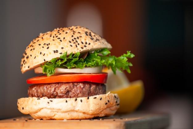 Delizioso hamburger fatto in casa con verdure fresche in cucina pronto a servire e mangiare