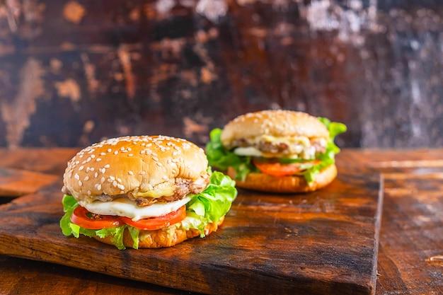 Delizioso hamburger fresco fatto in casa con lattuga, formaggio, cipolla e pomodoro su una tavola di legno rustica