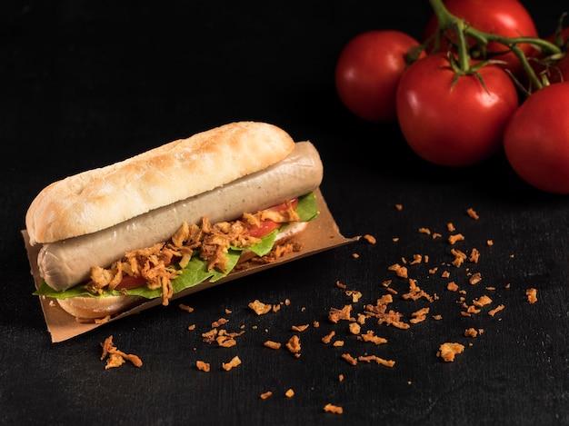 Delizioso hot dog fast-food su carta da forno e pomodori