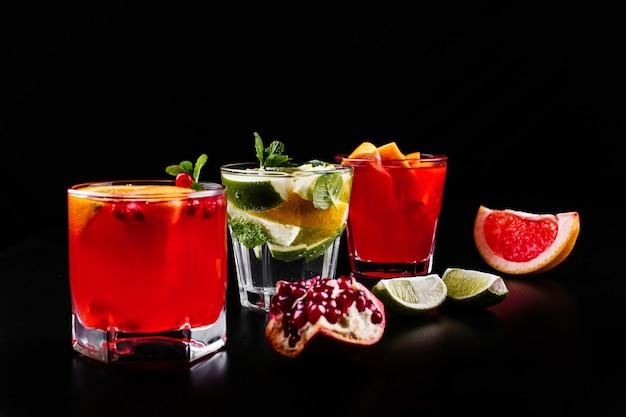 Delizioso mojito, rum e cola, arancia rossa e cocktail di vodka serviti con frutta