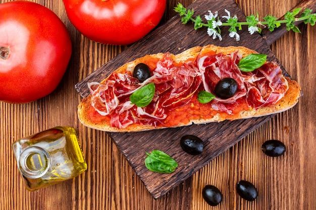 Delizioso pane tostato con pomodoro naturale, olio extra vergine di oliva, prosciutto iberico, olive nere e foglie di basilico.