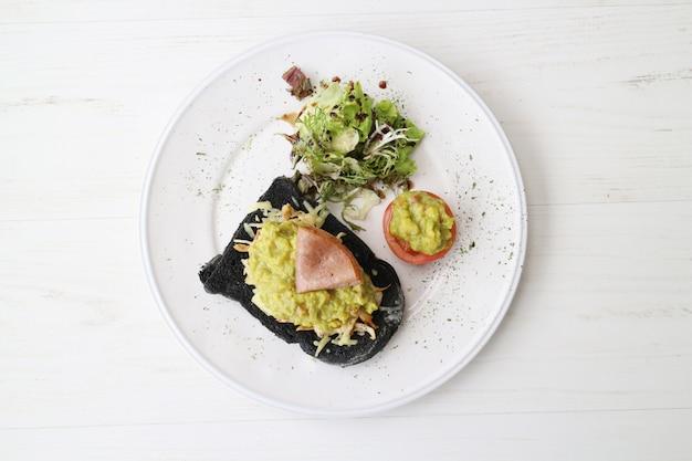 Delizioso panino al pane nero con insalata sul piatto bianco