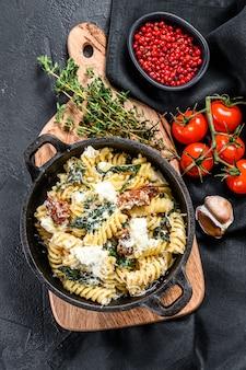 Delizioso piatto fusilli di pasta con salsa cremosa di spinaci e pomodori secchi