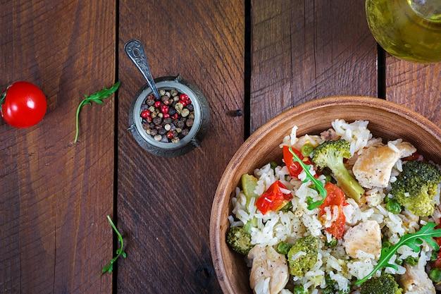Delizioso pollo, broccoli, piselli, pomodori saltati in padella con riso.
