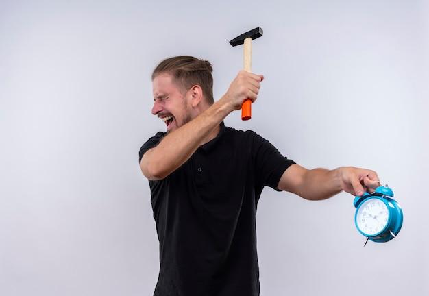 Deluso giovane uomo bello in maglietta polo nera con un martello andando a rompere la sveglia in mano con espressione aggressiva sul viso in piedi su sfondo bianco