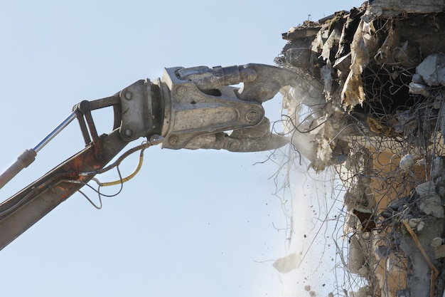 Demolizione di condominio in cemento con escavatore idraulico / gru idraulica. fare spazio per il nuovo edificio.