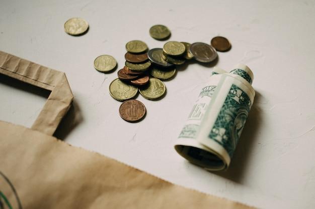 Denaro contante dollari, monete in euro con un pacchetto kraft su sfondo bianco.