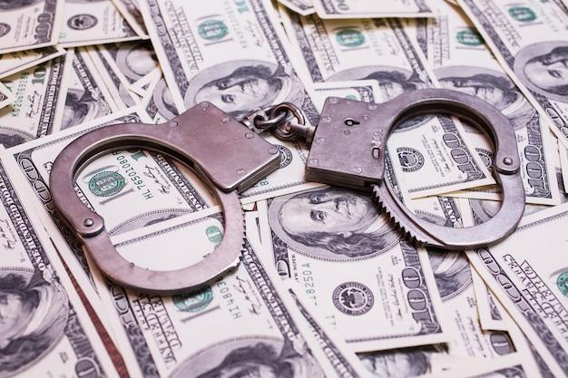 Denaro e legge, manette sul denaro, banconote da cento dollari sul lato frontale e manette. sfondo di dollari, risparmi, tasse e legge
